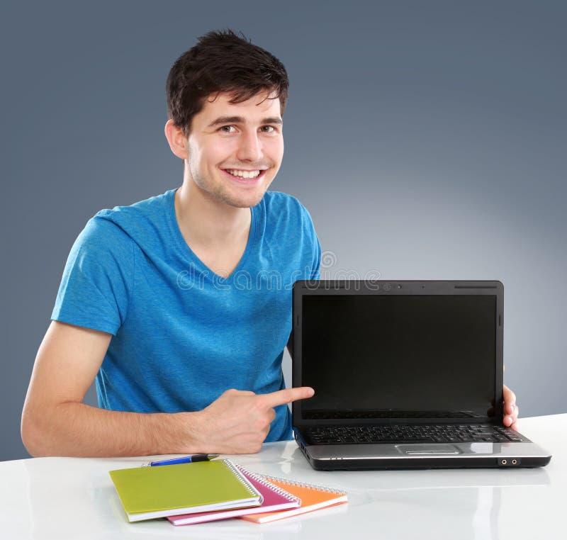 Męski uczeń pokazuje pustego ekran laptop zdjęcia royalty free