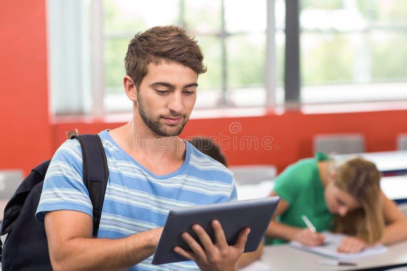 Męski uczeń używa cyfrową pastylkę w sala lekcyjnej zdjęcie stock