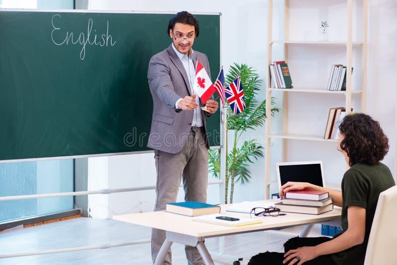 Męski uczeń w sali lekcyjnej i nauczyciel angielskiego zdjęcie royalty free