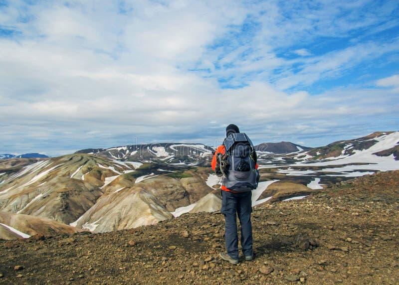 Męski wycieczkowicz wycieczkuje samotnie w dzikiego podziwia powulkanicznego krajobraz z ciężkim plecakiem Podróży styl życia prz obraz stock