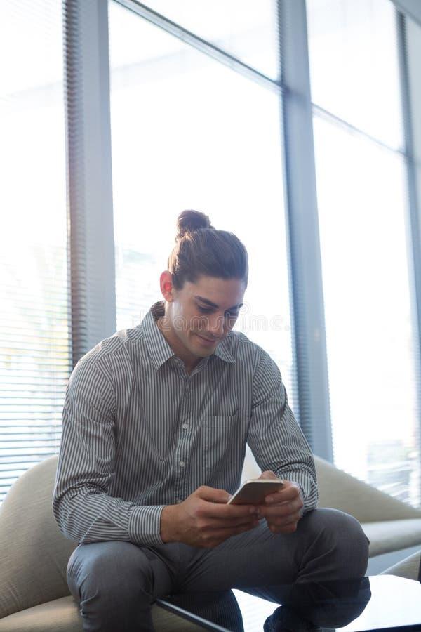 Męski wykonawczy używa telefon komórkowy w czekanie terenie zdjęcia royalty free