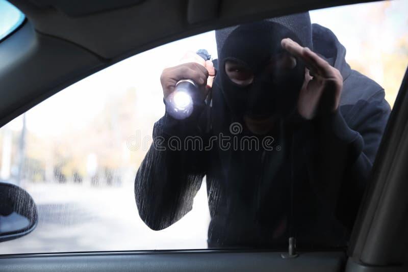 Męski złodziej patrzeje wśrodku samochodu z latarką obraz royalty free