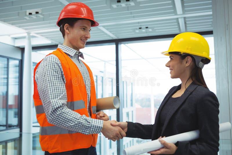 Męskie architekta chwiania ręki z bizneswomanem obrazy stock