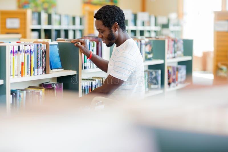 Męskie Bibliotekarskie ułożenie książki W Bookstore obrazy royalty free