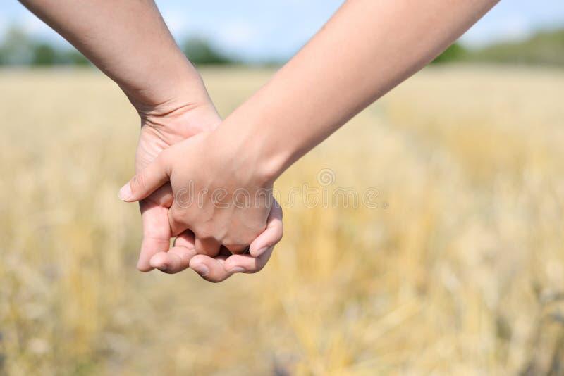 Męskie i żeńskie mienie ręki nad polem zdjęcie royalty free