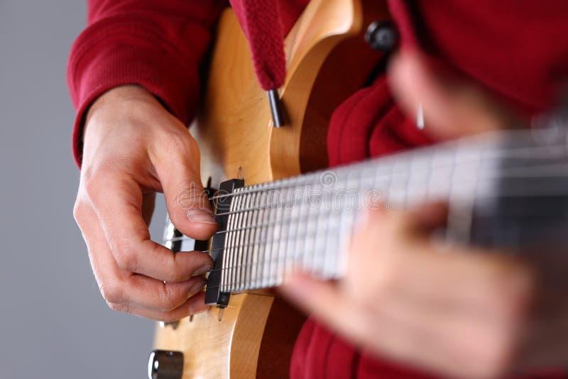 Męskie ręki bawić się klasyczną kształt gitarę elektryczną obraz royalty free