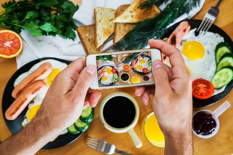Męskie ręki biorą obrazek Amerykański śniadanie na telefonu odgórnym widoku zdjęcie stock