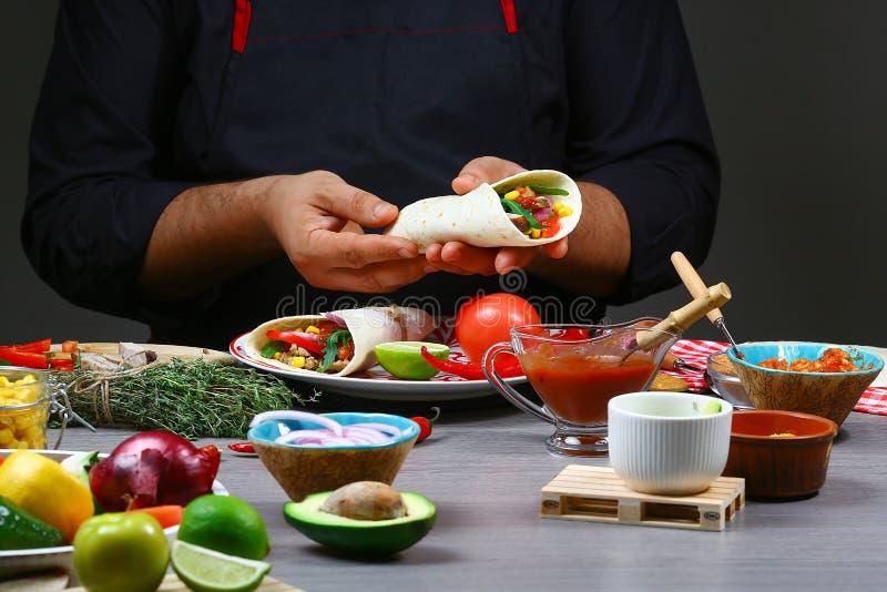 Męskie sprzedawca uliczny ręki robi taco Meksykańska kuchnia przekąsza, gotujący fast food dla handlowej kuchni obraz royalty free