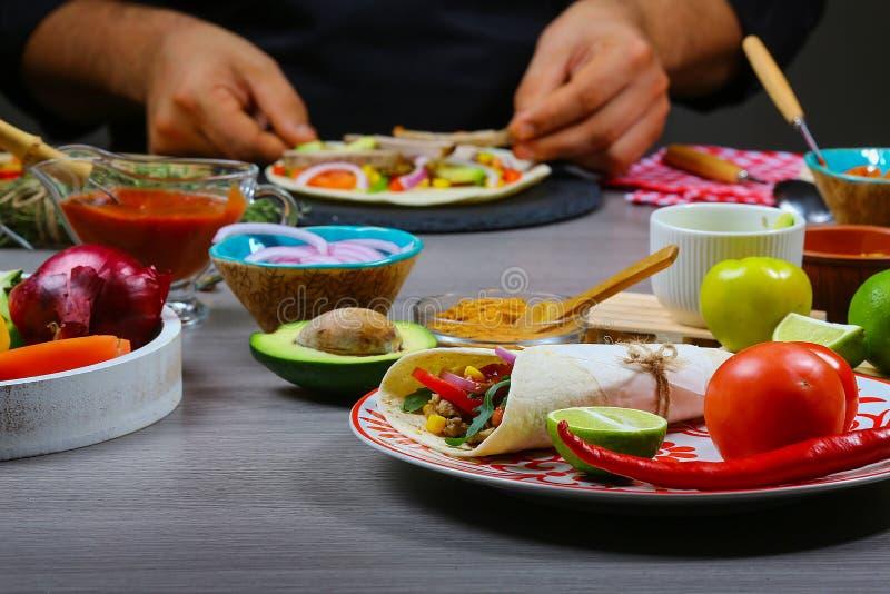 Męskie sprzedawca uliczny ręki robi taco Meksykańska kuchnia przekąsza, gotujący fast food dla handlowej kuchni fotografia stock
