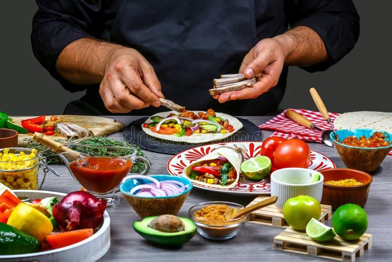 Męskie sprzedawca uliczny ręki robi taco Meksykańska kuchnia przekąsza, gotujący fast food dla handlowej kuchni obrazy stock