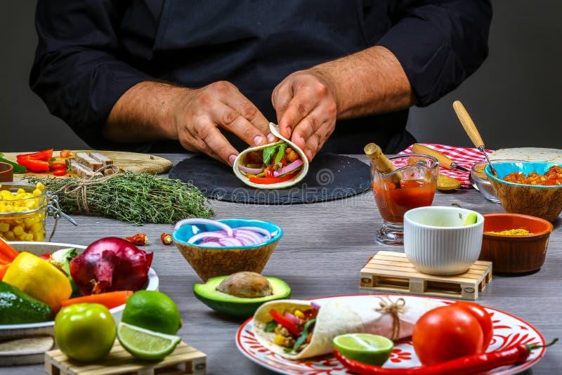 Męskie sprzedawca uliczny ręki robi taco Meksykańska kuchnia przekąsza, gotujący fast food dla handlowej kuchni pojęcie kulinarny zdjęcie stock