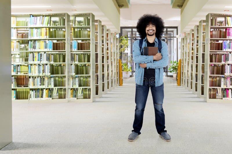 Męskiego Afro studencka pozycja w bibliotece obraz stock