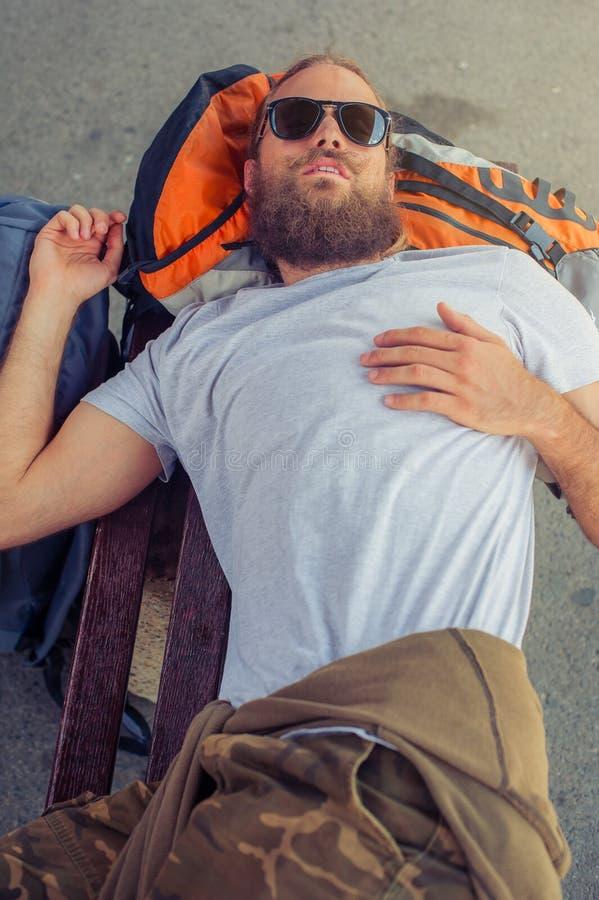 Męskiego backpacker turystyczny drzemanie na ławce zdjęcie royalty free