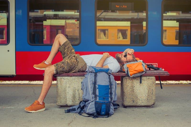 Męskiego backpacker turystyczny drzemanie na ławce fotografia stock