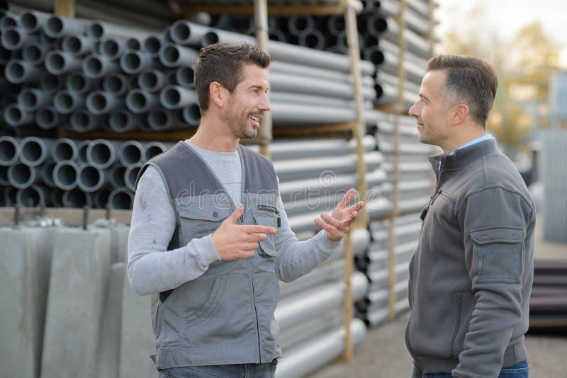 2 męskiego coleagues gawędzi przy fajczanym fabrycznym jardem zdjęcie royalty free