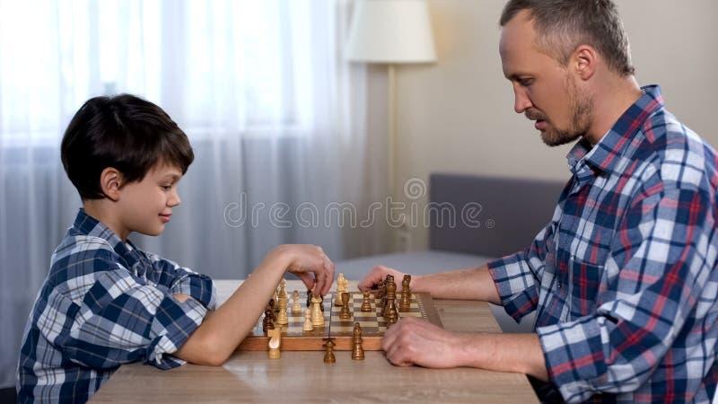 Męskiego dziecka poruszający szachy na pokładzie, bawić się grę z ojcem, ulubiony hobby zdjęcia stock