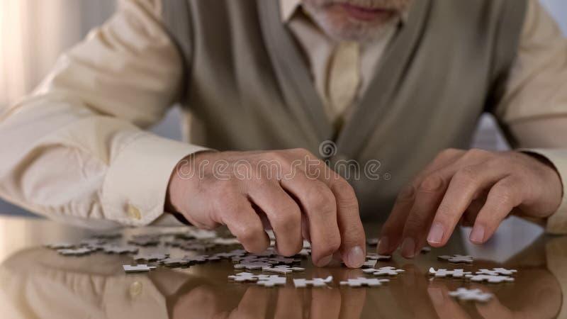 Męskiego emeryta wyrzynarki gromadzić łamigłówka w domu, Alzheimer rehabilitacja, hobby zdjęcie royalty free
