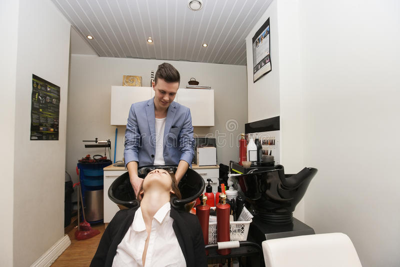 Męskiego hairstylist klienta płuczkowy żeński włosy w piękno salonie zdjęcie royalty free