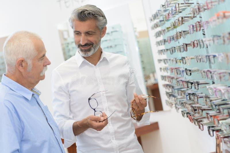 Męskiego oftalmologa pomaga klient w optyka sklepie fotografia royalty free