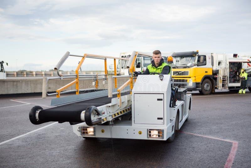 Męskiego pracownika bagażu konwejeru Napędowa ciężarówka Na Lotniskowym pasie startowym fotografia royalty free