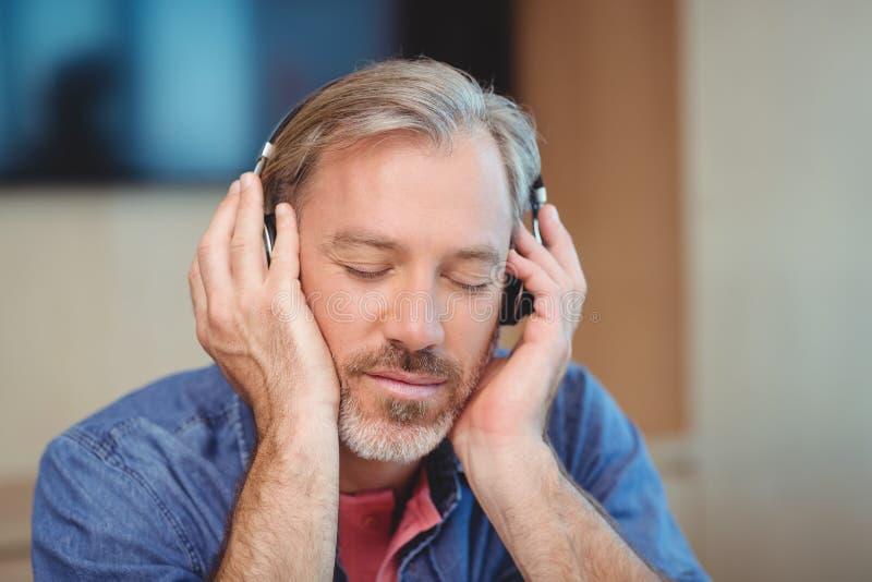 Męskiego projektant grafik komputerowych słuchająca muzyka na hełmofonach zdjęcia stock
