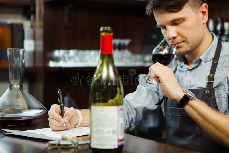 Męskiego sommelier smaczny czerwone wino i robić przy baru kontuarem notatki zdjęcie royalty free