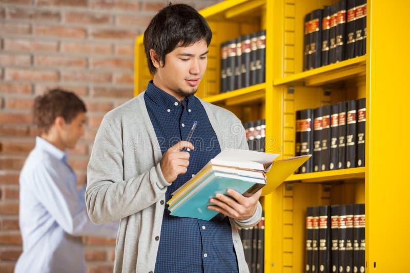 Męskiego ucznia Czytelnicza książka W szkoły wyższa bibliotece obrazy stock