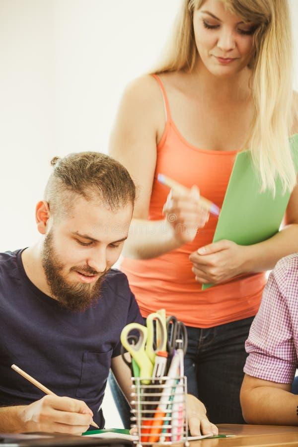 Męskiego ucznia i nauczyciela adiunkt w sala lekcyjnej zdjęcia stock