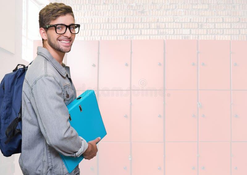 męskiego ucznia mienia falcówka przed szafkami zdjęcia stock