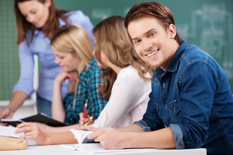 Męskiego ucznia mienia książka Z kolega z klasy I nauczycielem Przy biurkiem zdjęcia royalty free