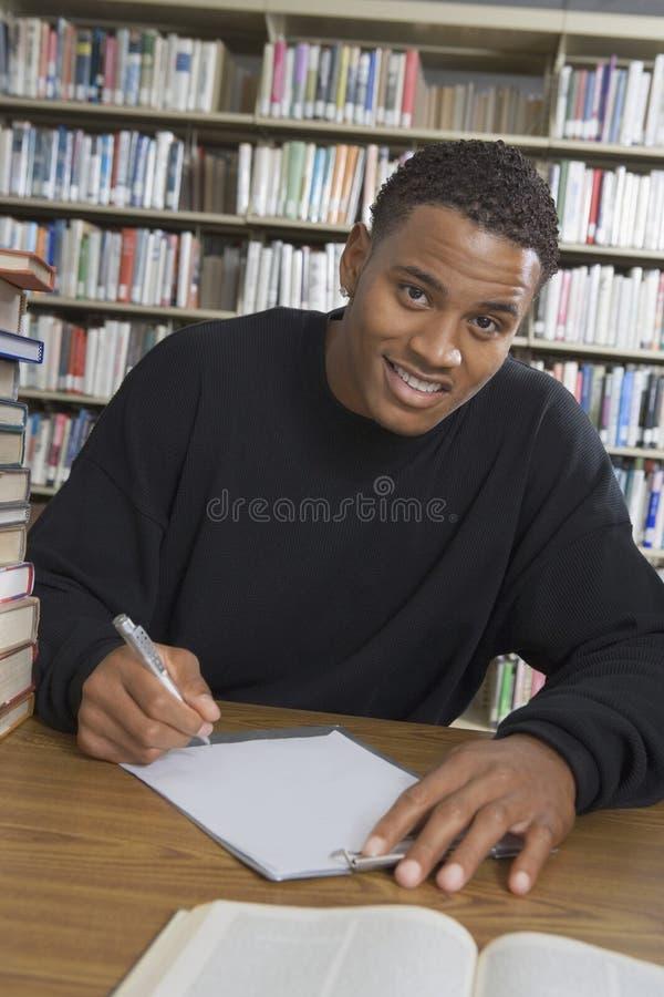 Męskiego ucznia studiowanie W szkoły wyższa bibliotece fotografia stock