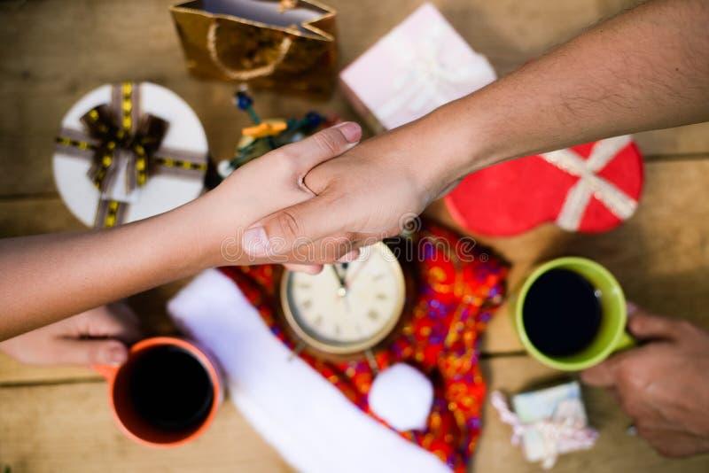 Męskiej ręki potrząsalnej żeńskiej ręki above stół z obraz stock