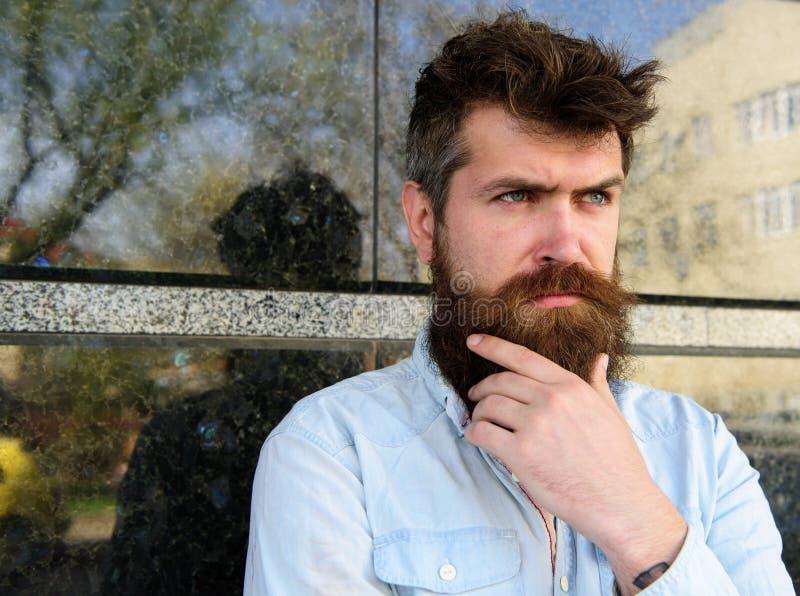 Męskości pojęcie Modniś z kudłacącym włosy dotyka brodę podczas gdy patrzejący w odległość Facet patrzeje podejrzanym 308 mosiężn obraz royalty free