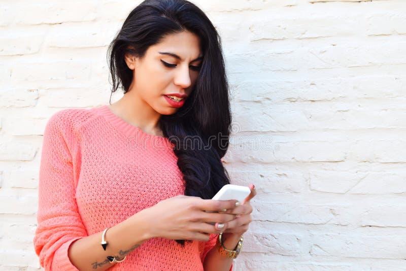 Młoda łacińska kobieta używa jej telefon komórkowego fotografia royalty free