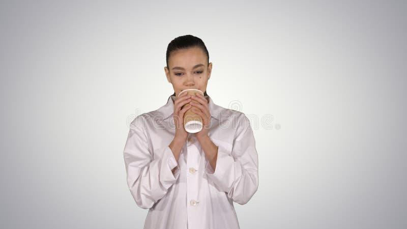 Młoda łacińska lekarka ma przerwę i pije kawę na gradientowym tle obrazy royalty free