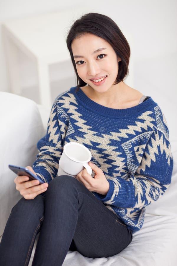 Młoda ładna Azjatycka kobieta z mądrze telefonem. obrazy royalty free