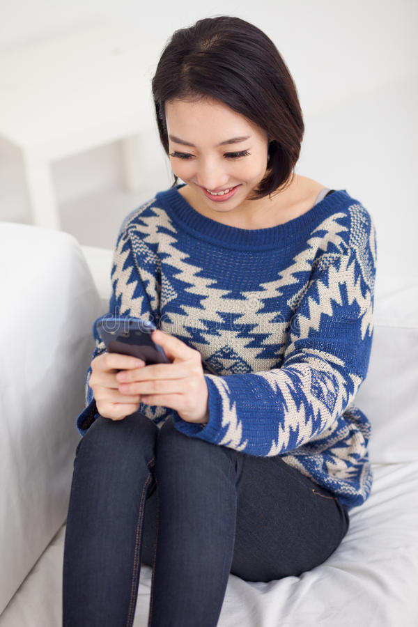 Młoda ładna Azjatycka kobieta z mądrze telefonem. fotografia royalty free