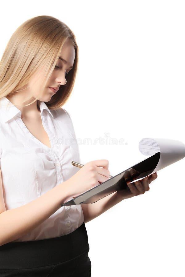 Młoda ładna biznesowa kobieta robi notatkom na schowku obraz stock