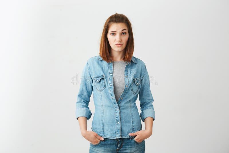 Młoda ładna brunetki dziewczyna patrzeje kamerę z pogardy dźwigania brwią up nad białym tłem fotografia stock