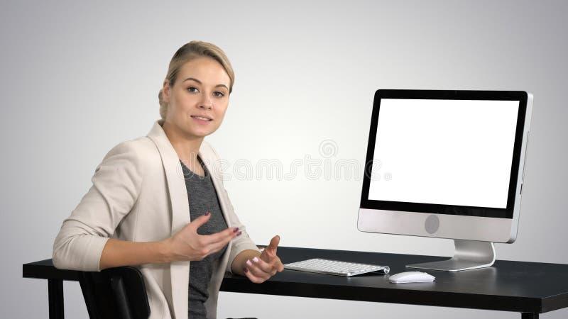Młoda ładna dama opowiada kamera i pokazuje coś na ekranie komputer na gradientowym tle obraz stock