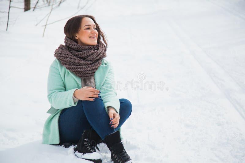 Młoda ładna dama w ciepłych ubraniach siedzi na białym śniegu na zima dniu zdjęcie stock