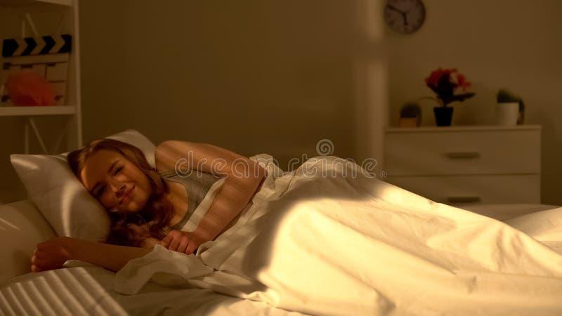 Młoda ładna dziewczyna budzi się w łóżkowym, uśmiechniętym i dobrym nastroju w ranku, pozytyw zdjęcie royalty free