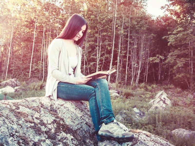 Młoda ładna dziewczyna czyta książkowego obsiadanie na wielkiej skale w lesie zdjęcie royalty free