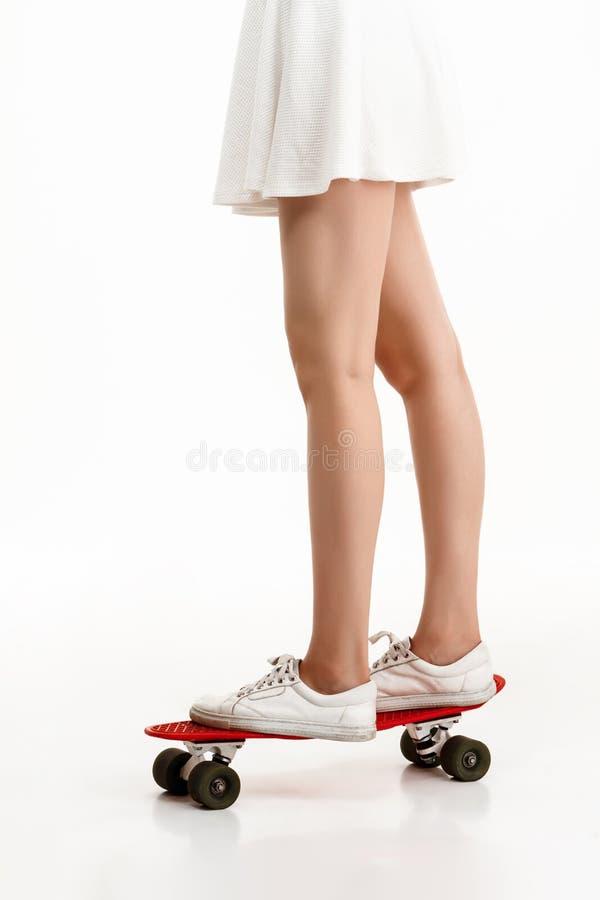 Młoda ładna dziewczyna jeździć na deskorolce nad białym tłem z bliska obraz royalty free