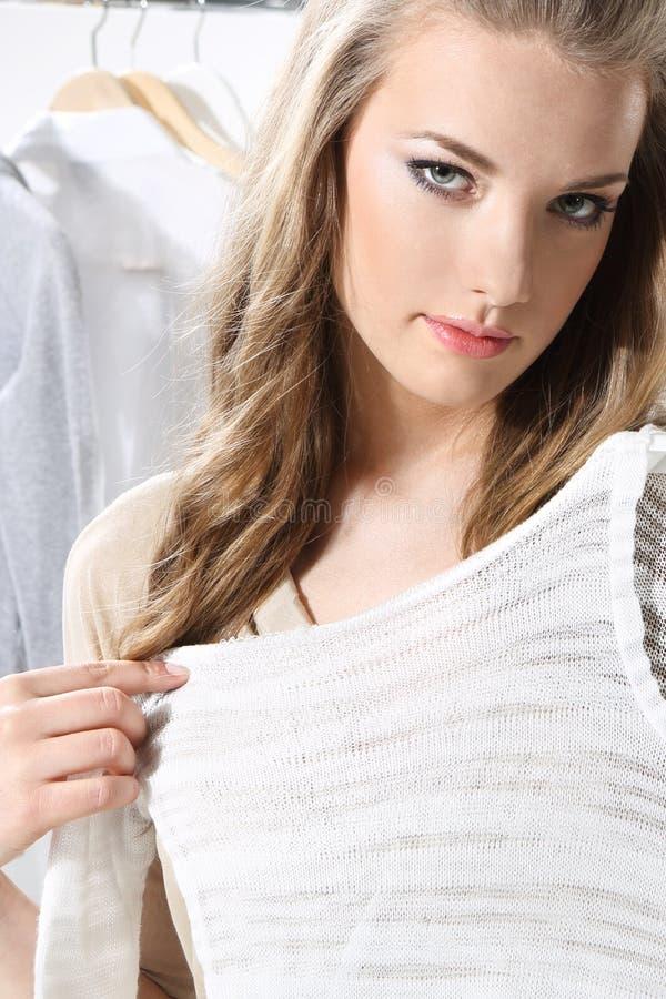 Ładna dziewczyna próbuje na odziewa fotografia stock