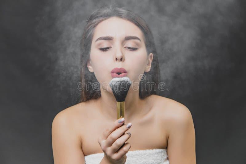 Młoda ładna dziewczyna trzyma muśnięcie dla makeup w ona ręki To dmucha daleko od proszek dla makijażu muśnięcia i spojrzenia prz zdjęcia royalty free