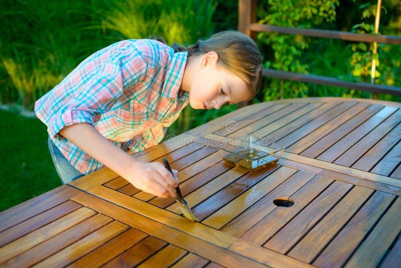 Młoda ładna dziewczyna trzyma szczotkarską stosuje lakierniczą farbę na drewnianym ogródu stole obrazy stock