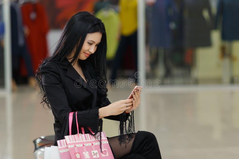 Młoda ładna dziewczyna trzyma torba na zakupy i używa mądrze telefon w centrum handlowym fotografia stock