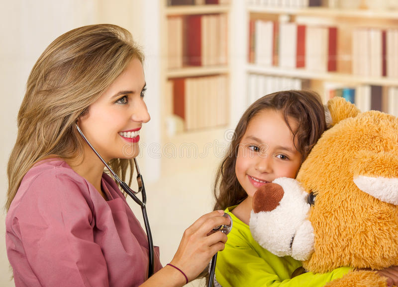 Młoda ładna dziewczyna uśmiecha się jej misia i ściska podczas gdy piękna uśmiechnięta lekarka egzamininuje z stetoskopem w a zdjęcia stock