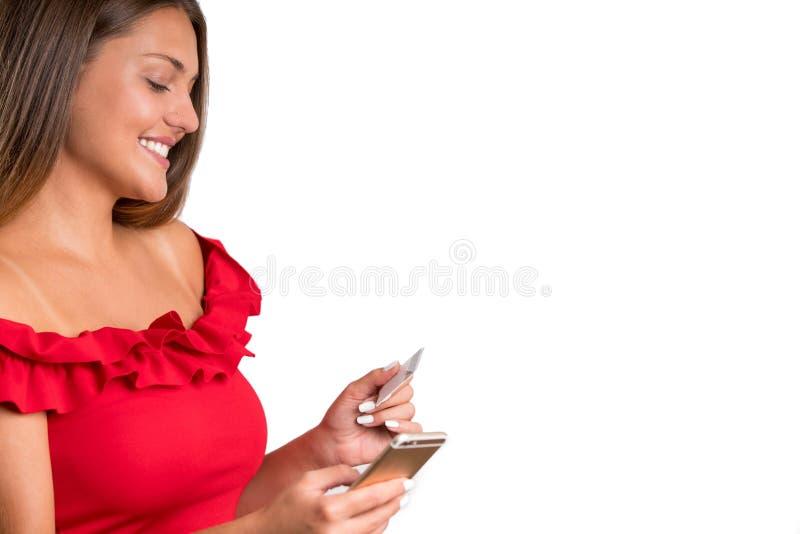 Młoda ładna dziewczyna w czerwieni sukni mienia kredyta telefonie i bardzie odosobniony zdjęcie stock